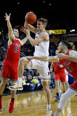 Michigan guard Cole Bajema (22) drives on Saginaw Valley State's James Toohey (15), of Australia, during the first half of an NCAA exhibition college basketball game in Ann Arbor, Mich., Friday, Nov. 1, 2019.