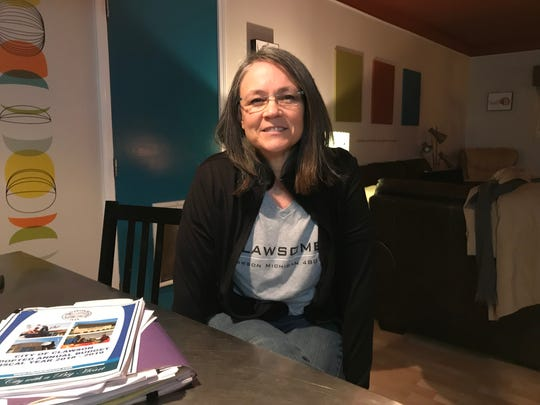 Clawson mayoral candidate Reese Scripture sits in her dining room in 2018 beside some of the legal briefs involved in her successful lawsuit that forced the city to be more transparent.