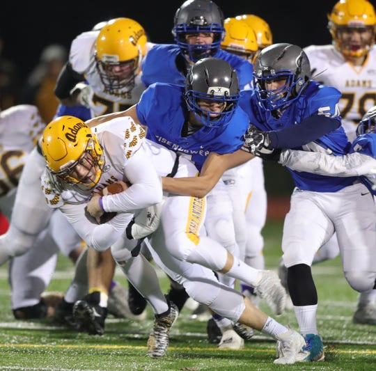 Rochester Adams high schools Carter Ferris is tackled by  Utica Eisenhower high schools Steven Nadolski during first half action Friday, November 1, 2019 at Utica Eisenhower high school in Utica, Mich.