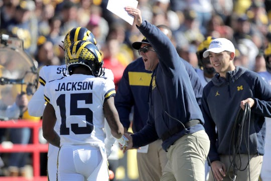 Michigan coach Jim Harbaugh, center, congratulates Giles Jackson after he returned the opening kickoff from Maryland for a touchdown during the first half of an NCAA college football game, Saturday, Nov. 2, 2019, in College Park, Md. (AP Photo/Julio Cortez)
