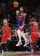 The Detroit Pistons' Derrick Rose (25) passes the ball as the Chicago Bulls' Zach LaVine (8) and Kris Dunn (32) defend in the first quarter at the United Center in Chicago on Friday, Nov. 1, 2019.