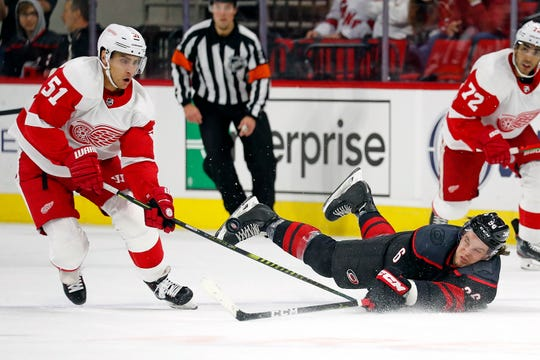 Carolina Hurricanes' Erik Haula (56) dives to the ice for the puck in front of Detroit Red Wings' Valtteri Filppula (51) during the first period of an NHL hockey game in Raleigh, N.C., Friday, Nov. 1, 2019.