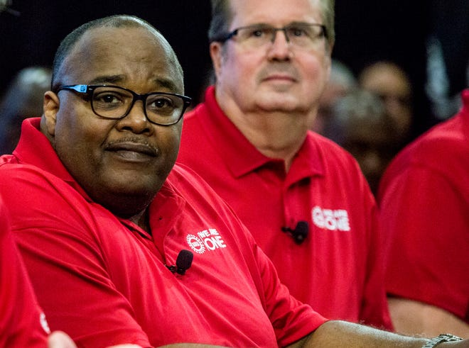 From left, Rory Gamble, UAW vice president and national Ford director, takes his place at the table beside United Auto Workers (UAW) union President Gary Jones during the Ford UAW contract ceremonial handshake at Ford World Headquarters in Dearborn, Mich., Monday, July 14th, 2019.