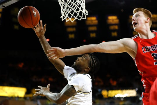 Michigan guard Zavier Simpson (3) is fouled by Saginaw Valley State's Jarno Pomstra (32), of the Netherlands, during the first half of an NCAA exhibition college basketball game in Ann Arbor, Mich., Friday, Nov. 1, 2019.
