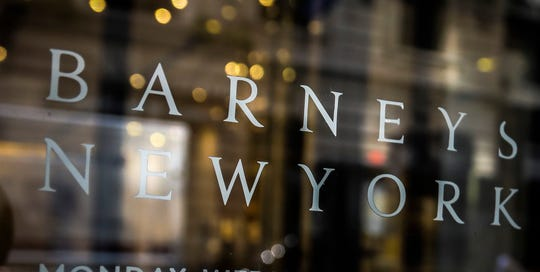 FILE - In this July 16, 2019, file photo signage for Barneys New York department store is displayed on the store's window in New York.