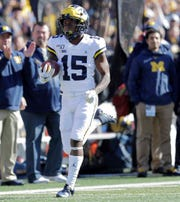 Michigan's Giles Jackson returns the opening kickoff for a touchdown during the first half.