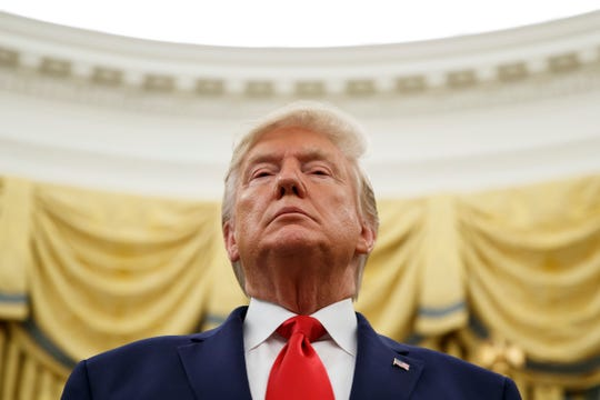 FILE - In this Oct. 24, 2019 file photo, President Donald Trump stands during a Presidential Medal of Freedom ceremony for auto racing great Roger Penske in the Oval Office of the White House in Washington. (AP Photo/Alex Brandon)