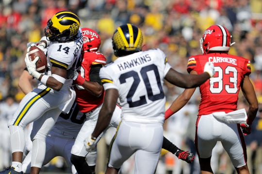 Michigan defensive back Josh Metellus (14) intercepts a pass from Maryland quarterback Josh Jackson, as Maryland's Sean Savoy tries to bring him down during the first half.