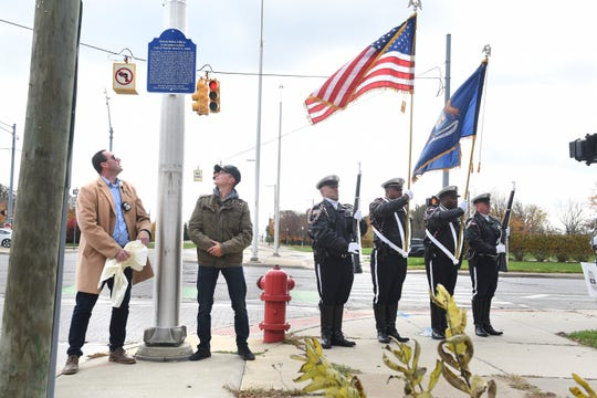 Chris Powell, left, president of the officer Collin Rose Foundation, and Jacob Fournier, grandson of Police officer Scott Larkin, unveil a memorial marker in honor of Detroit Police officer Scott Larkin placed at East Grand and East Jefferson in Detroit on Saturday, November 2, 2019.