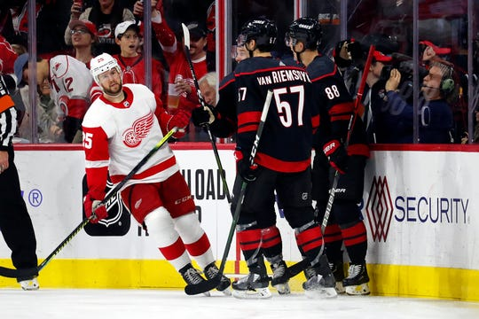 The Hurricanes congratulate Sebastian Aho on his goal as the Red Wings' Mike Green skates past during the second period.