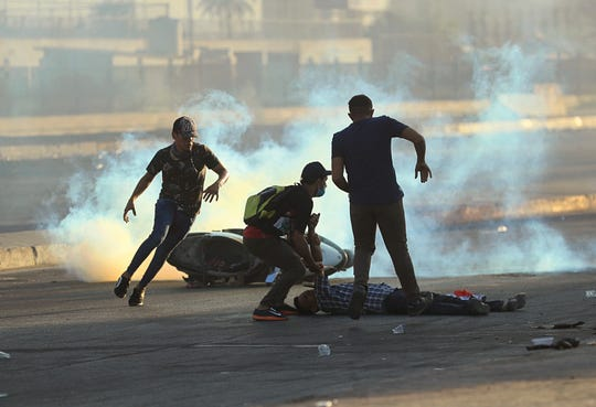 Anti-government protesters rush to an injured protestor during a demonstration in Baghdad, Iraq, Saturday, Oct. 5, 2019. The spontaneous protests which started