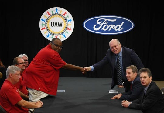 UAW's Rory Gamble and Jim Hackett, President and CEO of Ford Motor Company, shake hands at the start of contract negotiations.