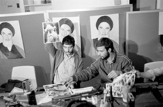 Ebrahim Asgharzadeh, left, a representative of the Iranian students who stormed the U.S. Embassy on Nov. 4, 1979, holds up a portrait of one of the blindfolded hostages, during a news conference Nov. 5 in the embassy in Tehran.