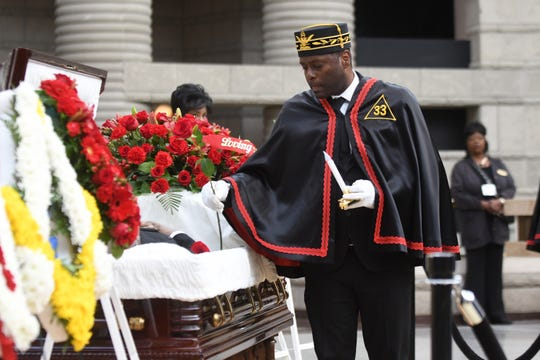 Kenneth Carter, of the Wolverine Consistory # 6 Valley of Detroit,  speaks of former Congressman John Conyer Jr. and places a rose in the casket during a visitation ceremony held at the Charles H. Wright Museum of African American History in Detroit on Saturday, November 2, 2019. Max Ortiz, The Detroit News