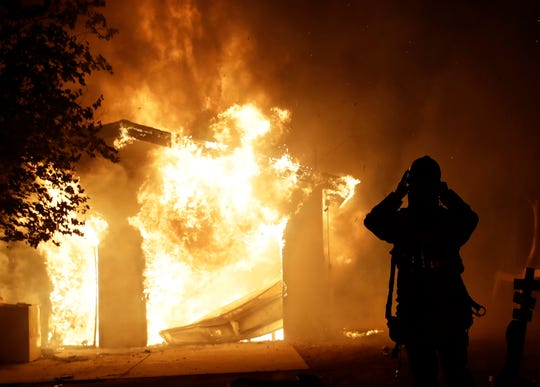 A firefighter prepares to fight a wildfire as it overtakes a home Thursday, Oct. 24, 2019, in Santa Clarita, Calif.