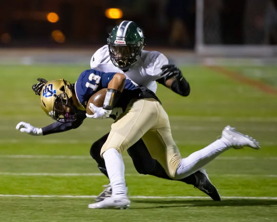 Grosse Point South's A.J. Benson (13) is tackled by Cass Tech's Donny Scott (6) in the first half.