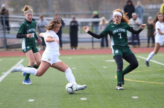 Ellie Mustico kicks the ball ahead for Elmira Notre Dame as Unatego's Leah Hamm defends during the Section 4 Class C girls soccer final Nov. 2, 2019 at Norwich.