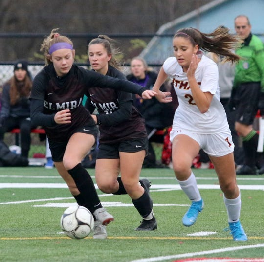 Elmira's Jodie White (left) and Ireland Krawczyk (center) chase after the ball with Ithaca's Ava Chouman during the Section 4 Class AA girls soccer final Nov. 1, 2019 at Waverly Memorial Stadium.
