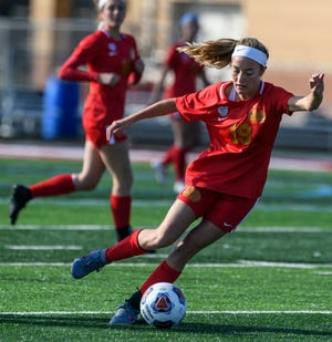 Mater Dei's Miranda Nosko (19) kicks the ball towards the Fort Wayne Bishop Dwenger Saints' goal during the IHSAA Class 2A girls state soccer championship at Fishers High School in Fishers, Ind., Saturday, Nov. 2, 2019