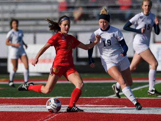 Mater Dei's Este Bonnell (2) keeps the ball away from Fort Wayne Bishop Dwenger's McKenna Kleinrichert (19) during the first half of the IHSAA Class 2A girls state soccer championship at Fishers High School in Fishers, Ind., Saturday morning, Nov. 2, 2019.