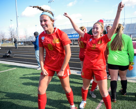 Mater Dei's Emma Lamble (8) and Mater Dei's Jill Happe (3) cheer with their teammates after winning the IHSAA Class 2A girls state soccer championship at Fishers High School in Fishers, Ind., Saturday, Nov. 2, 2019.