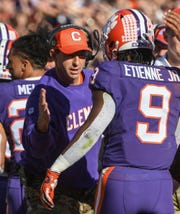 Clemson Head Coach Dabo Swinney congratulates running back Travis Etienne (9) for his touchdown during the first quarter at Memorial Stadium with Wofford in Clemson, South Carolina Saturday, November 2, 2019.