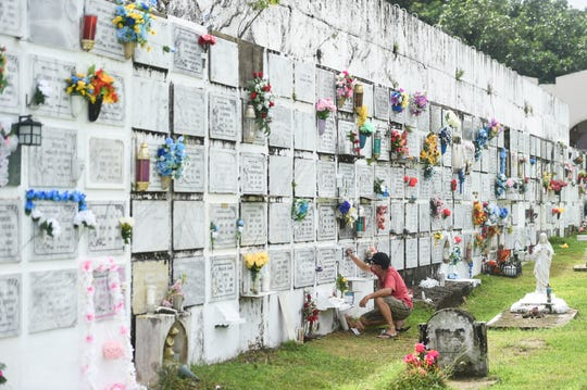 Families prepare their loved ones' memorial plaques for All Souls' Day at Pigo Catholic Cemetery in Hagåtña on Nov. 2, 2019.