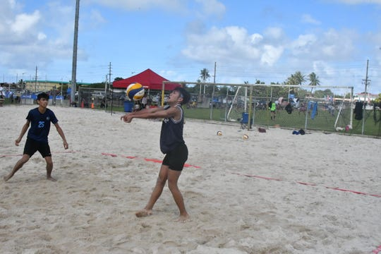 Saint Paul's Keith Nauta passes the ball to teammate Ethan Saulog in their match against GW's Louis Montejo and Matthew Magaling during IIAAG Boys Beach Volleyball action Nov. 2 at the Guam Football Association's sand courts.