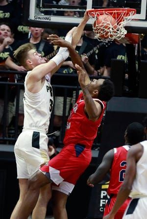Purdue center Matt Haarms, left, dunks over Southern Indiana forward Josh Price during an exhibition NCAA college basketball game Friday, Nov. 1, 2019, in West Lafayette, Ind. (AP Photo/R Brent Smith)