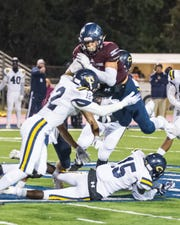 St. Thomas More wide receiver Jack Bech (7) tries to go over the top as the Carencro Bears play the St. Thomas More Cougars on Friday, Nov. 1, 2019.