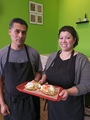 José and Carolyn Salazar, holding their signature dish, tostadas, Friday, Nov. 1, 2019, have just opened Two Tostadas restaurant in Lyon Twp.