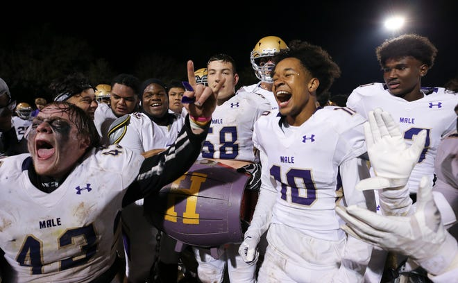 Male celebrated with the wooden barrel after they defeated Manual during their game at the Manual Stadium in Louisville, Ky. on Nov. 1, 2019.