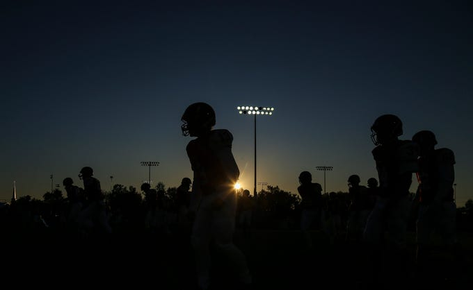 Jeff players warm up before playing rival New Albany in sectional football Friday evening in Jeffersonville.