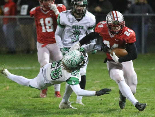 Shelby's Owen Fisher delivers a stiff arm to a Clear Fork defender during the Whippets' Mid-Ohio Athletic Conference championship win over Clear Fork on Friday night.