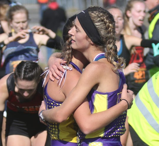 Lexington's Halle Hamilton and Lily Weeks share a hug after leading Lady Lex to its third consecutive state cross country championship on Saturday.
