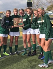 Some of Madison's soccer players celebrate with their Division II regional championship plaque after a 10-1 victory over Oak Harbor on Saturday.