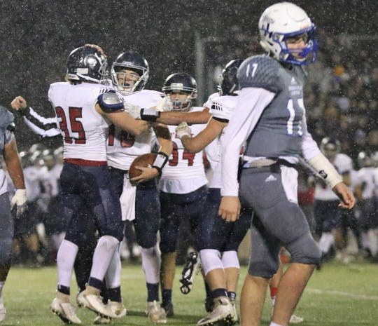 Brookfield East teammates celebrate with Sam McGath, center, after his interception against Brookfield Central in a Level 2 playoff game on November 1, 2019.
