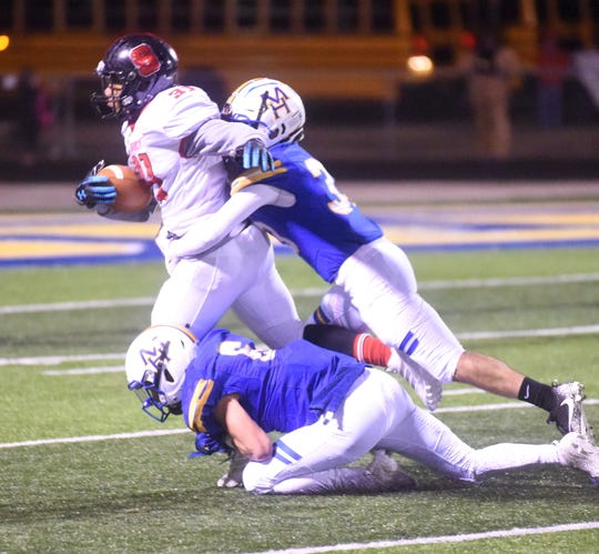 Mountain Home's Hunter Preis and Logen Walker tackle Searcy's Latreal Neal on Friday night.