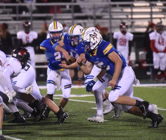 Mountain Home quarterback Lawson Stockton hands off to senior Blake Pope against Searcy on Friday night.