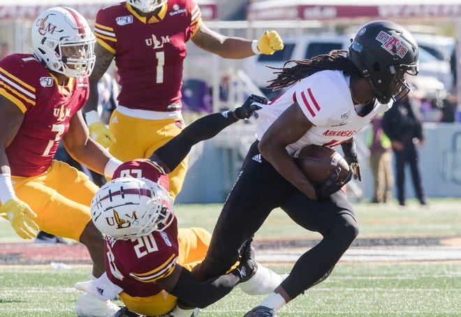 ULM's Josh Newton (20) attempts to bring down Arkansas State's Donovan Marshall (11) during the game at Malone Stadium in Monroe, La. on Nov. 2.