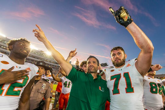Miami head coach Manny Diaz, center, and Miami defensive lineman Scott Patchan (71) celebrate their victory over Florida State in an NCAA college football game in Tallahassee, Fla., Saturday, Nov. 2, 2019. (AP Photo/Mark Wallheiser)