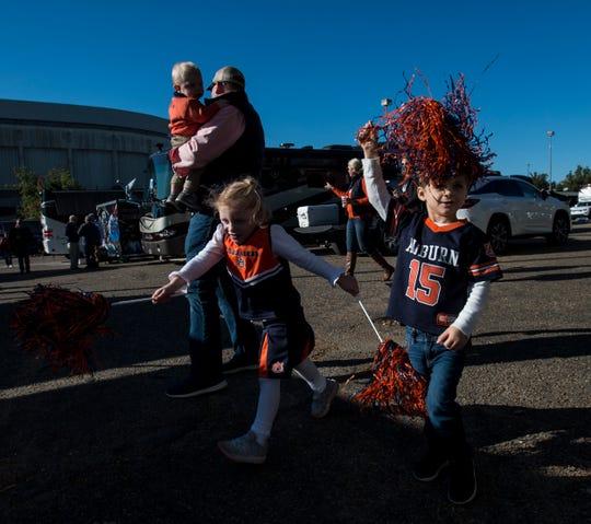 Addison Care Hicks, 4, and Aedin Andersen, 4, walk through tailgates at Jordan-Hare Stadium in Auburn, Ala., on Saturday, Nov. 2, 2019.