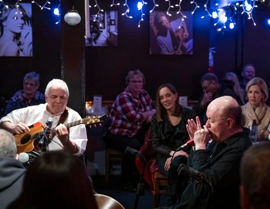 Jelly Roll Johnson, right, plays the harmonica at the Bluebird Cafe Friday November 1, 2019.  At left is Fred Knobloch and looking on from the center is his wife Mary Jo Johnson.