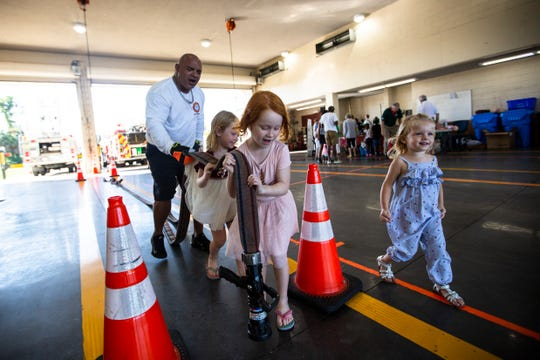 From right to left, Tara Peplau, 2, Nele Capuano, 5, and Pia Capuano, 3, carry a fire hose with the help of Eliseo Flecha during the Cape Coral Fire Department open house on Saturday, Nov. 2, 2019 at 4610 Coronado Parkway in Cape Coral.