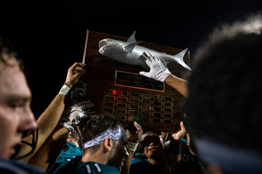 Gulf Coast High School hoist the Catfish Trophy after defeating Barron Collier 40-35, Friday, Nov. 1, 2019, at Gulf Coast High School in North Naples.