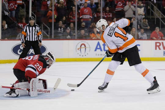 Philadelphia Flyers' Sean Couturier, right, scores past New Jersey Devils goaltender Mackenzie Blackwood during the shootout in an NHL hockey game in Newark, N.J., Friday, Nov. 1, 2019. The Flyers won 4-3.
