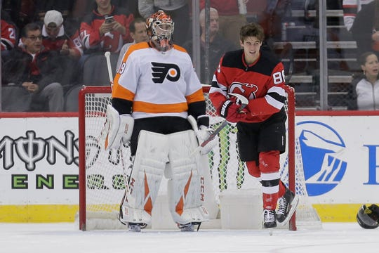 Philadelphia Flyers goaltender Carter Hart, left, watches as New Jersey Devils' Jack Hughes leaves the ice after a hard hit during the first period of an NHL hockey game in Newark, N.J., Friday, Nov. 1, 2019.