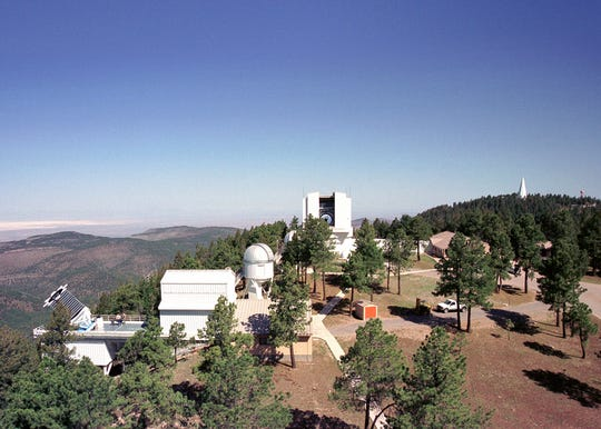 Apache Point Observatory, near Cloudcroft, New Mexico, is home to four telescopes: the 2.5 meter Sloan Foundation telescope (left); the 0.5 meter ARC Small Aperture Telescope and New Mexico State University's 1.0 meter telescope (center); and the 3.5 meter Astrophysical Research Consortium telescope (right). In the distance, the tiny spike above the trees to the far right is the National Solar Observatory.