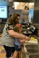 A parent helps her child chop and cook vegetables for a healthy meal.