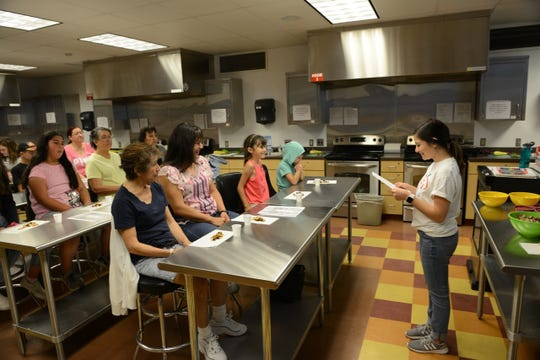 Families get together at the beginning of a Fit Families cooking class to go over a recipe.